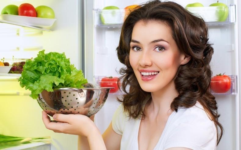 Девушка у холодильника с листьями салата