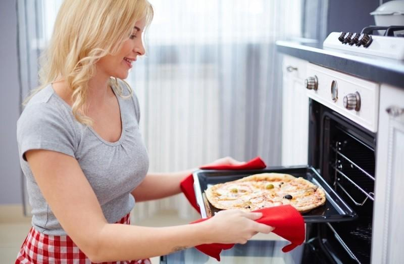 Девушка с пиццей возле газовой духовки