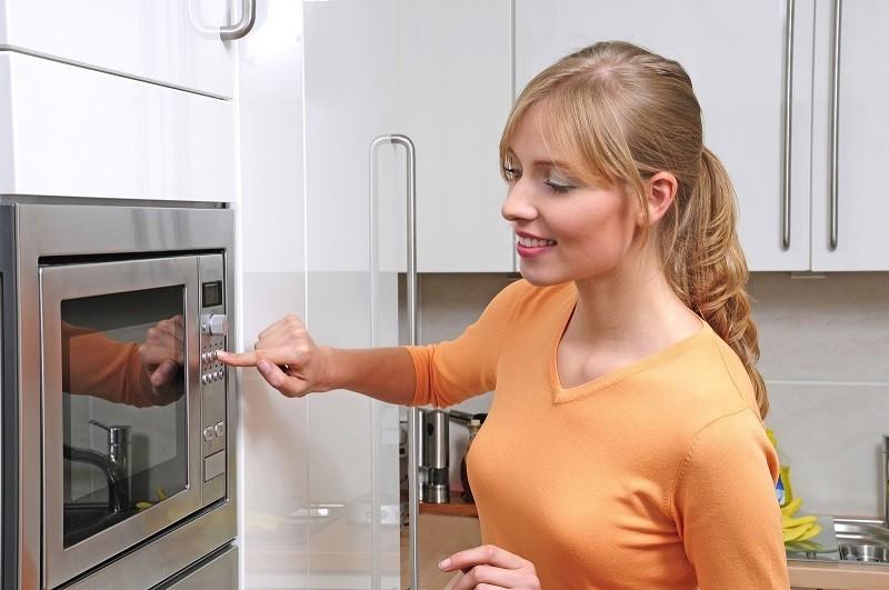 Девушка включает печь с грилем