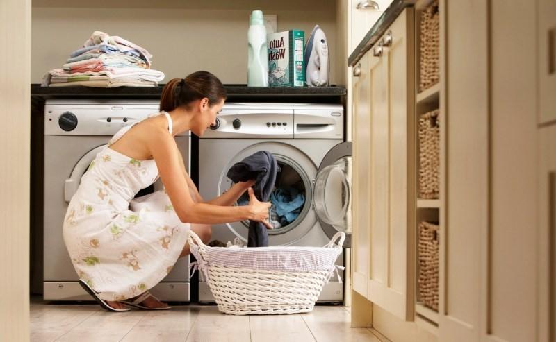 Стиральная машина, установленная на кухне, и женщина