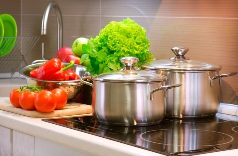 Кухонная плита, кастрюли, овощи и зелень