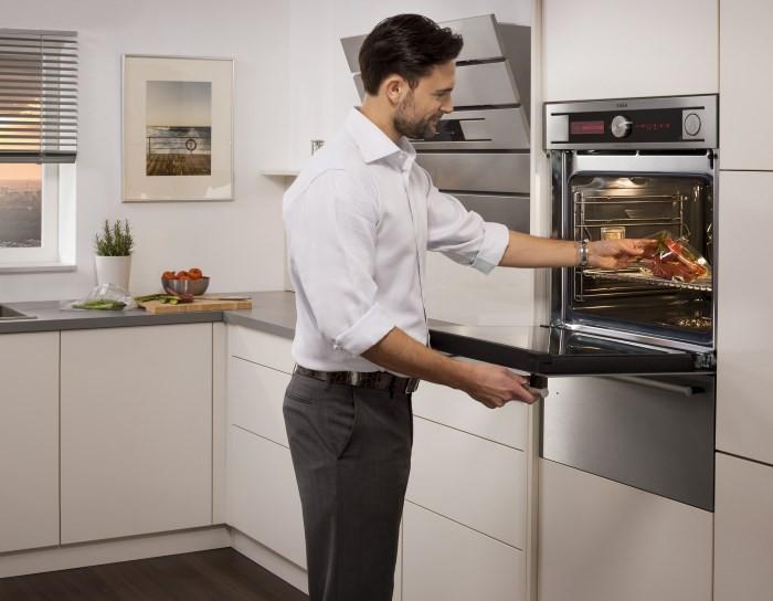 Встраиваемый духовой шкаф на кухне и мужчина
