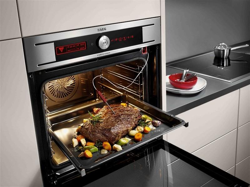 встраиваемый электрический духовой шкаф с куском запеченного мяса