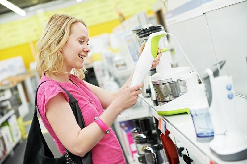 Девушка в магазине выбирает блендер