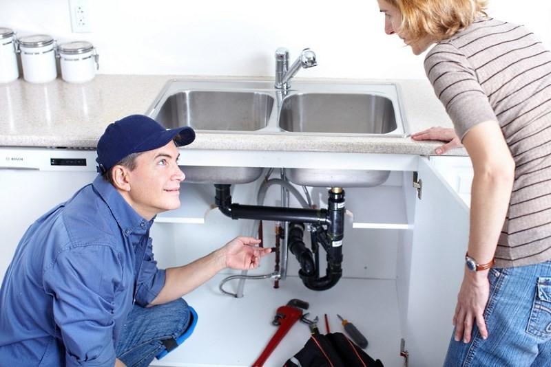 сантехник устанавливает сифон для раковины на кухне