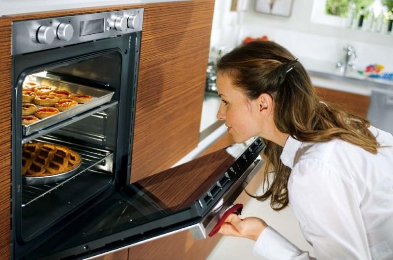 девушка печет булочки в духовке