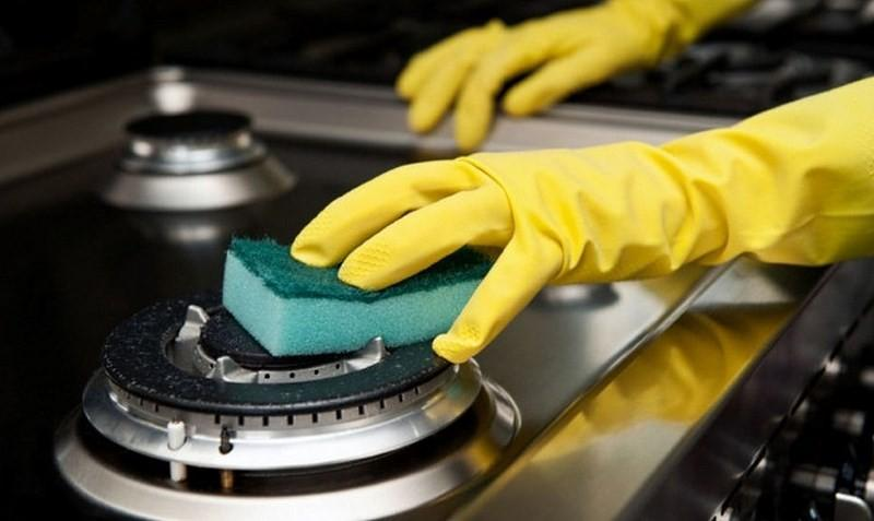 рука в перчатке трет губкой конфорку газовой плиты