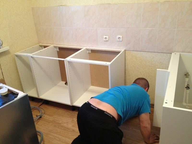 мужик собирает кухонные шкафы