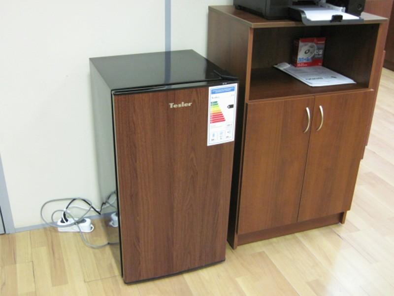 Маленький холодильник цвета темного дерева стоит в коридоре
