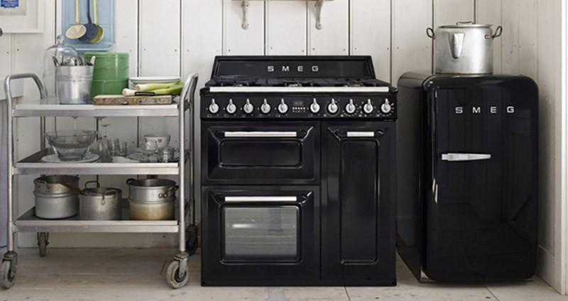 Маленький черный холодильник установлен в углу кухни
