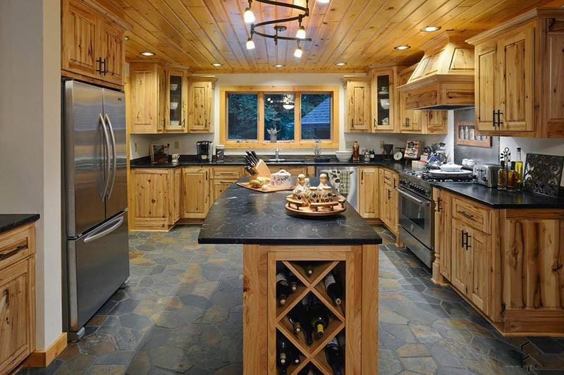 Каменный пол и кухонная мебель из светлого натурального дерева