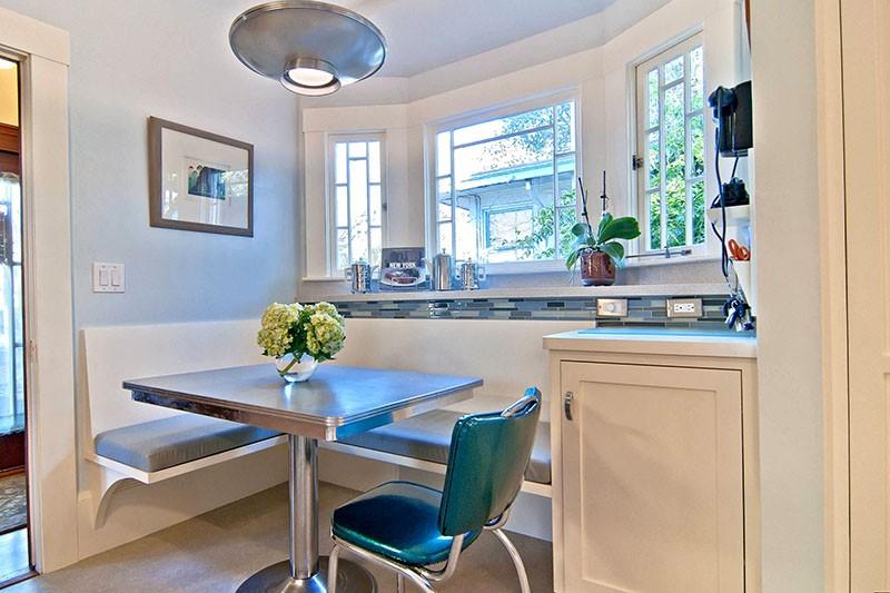Стол и стул металлических цветов, лампа-тарелка и угловой диван